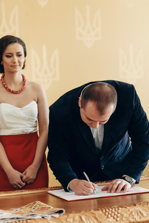 Handsome smiling groom in stylish suit signing marriage contract during wedding ceremony in registry office, newlywed family moment