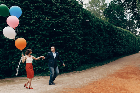 Cheerful groom in stylish clothes leading happy bride by her hand in a park, newlywed couple on a walk at the carnival with colorful balloons, fun honeymoon concept