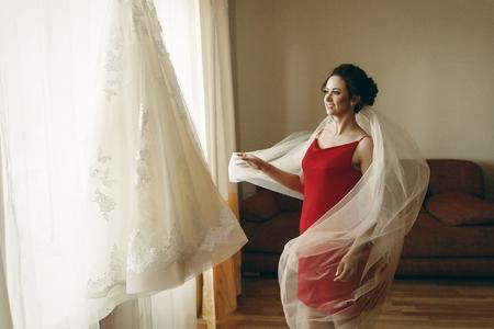 Mooie bruid in rode robe met sluier die de elegante witte kleding van het kanthuwelijk op hanger dichtbij een venster, de voorbereiding van het ochtendhuwelijk in hotel bekijken