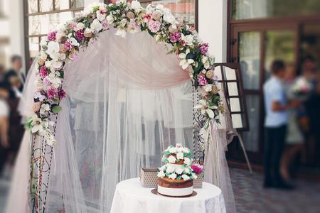 맛있는 장식 된 초콜릿 웨딩 케이크 꽃 화환 근처 결혼식 통로 야외, 의식 장식 개념