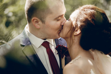 Portrait of beautiful brunette bride kissing handsome groom with red flower boutonniere face close-up, newlywed couple posing outdoors