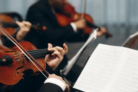 レストランでは、結婚披露宴で劇場演劇オーケストラ クローズ アップ、音楽のコンセプトでヴァイオリンとチェロを演奏のスーツでハンサムな男を