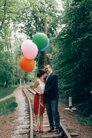 Beautiful portrait of fun newlywed couple with balloons, beautiful bride hugging with handsome groom near old railway in a park, travel concept