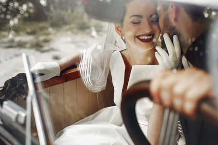 elegant gorgeous bride smiling and handsome stylish groom kissing her in car. unusual luxury wedding couple in retro style. romantic moment
