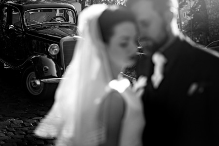 gorgeous elegant bride and stylish groom embracing, gentle touch in light. unusual luxury wedding in retro style. focus on car. unusual view. black white photo