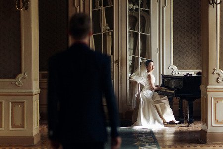 royal wedding: elegant stylish handsome groom looking at his gorgeous bride playing the piano. reflection in the mirror. unusual luxury wedding couple in retro style