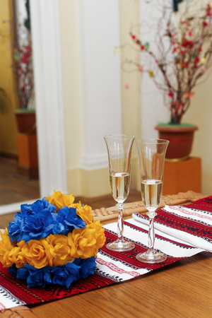 two glasses filled with champagne on table with blue and yellow flowers and ukrainian embroidered towel. official wedding registration ceremony in hall Stock Photo