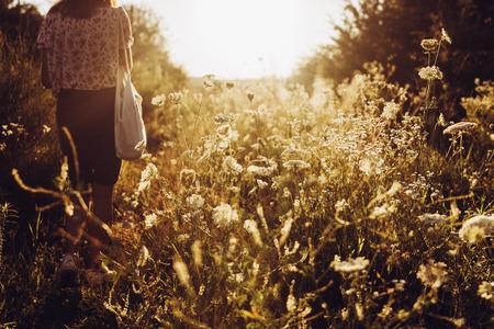 太陽光線の下で夏の夜の畑で野生の花の間で日光に歩いてエコバッグとスタイリッシュな流行に敏感な女性。自由奔放に生きる少女が草原でリラッ