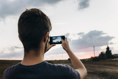 stylish hipster traveler holding smart phone taking photo of beautiful sunset landscape in summer field. instagram photography. exploring and discovering. space for text
