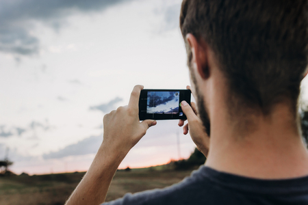 man hipster traveler taking photo holding smart phone, of beautiful sunset scenery in summer field. instagram photography. exploring and discovering. space for text. lifestyle