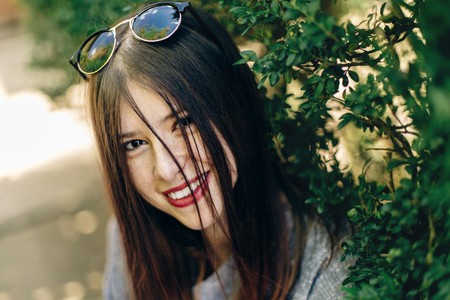 stylish beautiful hipster woman smiling near green leaves in sunny park. young girl with sunglasses with beautiful smile in botanical garden in spring. space for text. joyful moment Stock Photo