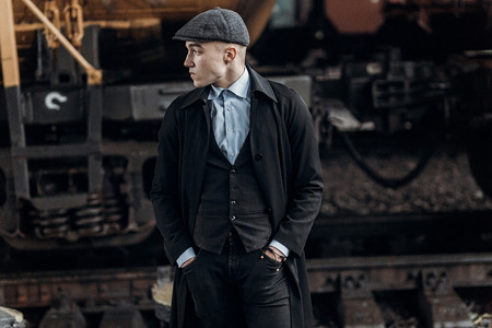 blinders: stylish gangster man posing on background of railway. england in 1920s theme. fashionable brutal confident guy. atmospheric  moments. space for text