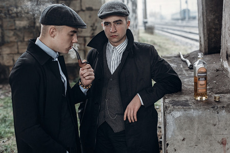 blinders: stylish gangsters men, smoking. posing on background of railway with bottle of alcohol. england in 1920s theme. fashionable brutal confident group. atmospheric  moments