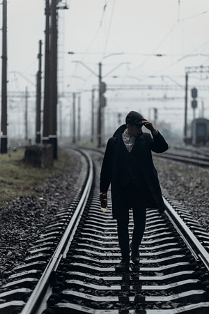 blinders: silhouette of stylish man in retro look walking in rain on background of foggy railway. england in 1920s theme. fashionable brutal gangster. atmospheric  moments. space for text