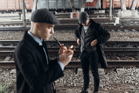 blinders: stylish gangsters men, smoking pipe on background of railway. england in 1920s theme. fashionable brutal confident group. atmospheric  moments. space for text