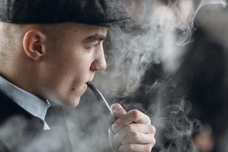 Hombre elegante en traje retro, fumando pipa de madera. sherlock holmes mira cosplay. inglaterra en el tema de los años 1920. gangster confidente de moda. momentos atmosféricos Foto de archivo - 75737486