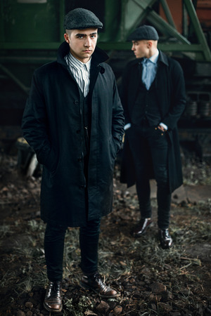 blinders: stylish gangster men in retro clothes posing on background of railway. england in 1920s theme. old fashionable look of brutal confident man