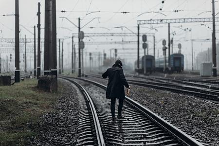 雨霧鉄道の背景の上を歩いてレトロな外観のスタイリッシュな男のシルエット。1920 年代をテーマにイギリス。ファッショナブルな残忍なギャング。