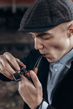 blinders: sherlock holmes look, man in retro outfit, smoking, lighting wooden pipe. england in 1920s theme. fashionable confident gangster. atmospheric moments. space for text
