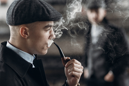 blinders: stylish man in retro outfit, smoking wooden pipe. sherlock holmes look cosplay.  england in 1920s theme. fashionable confident gangster. atmospheric moments