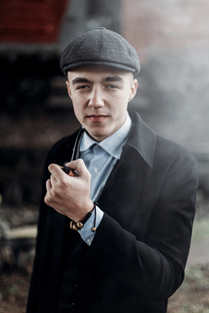 sherlock holmes look, man in retro outfit, smoking wooden pipe. england in 1920s theme. fashionable confident gangster. atmospheric moments. space for text