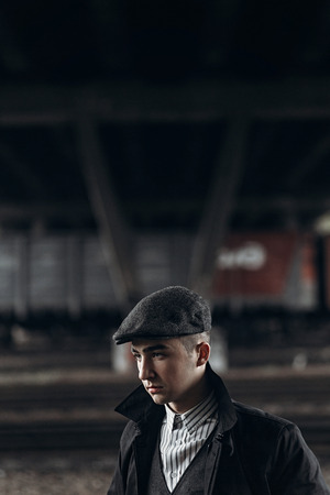 blinders: brutal gangster posing on background of railway. england in 1920s theme. fashionable confident man. atmospheric moments. Stock Photo