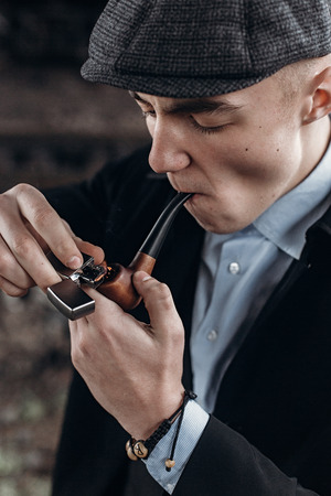 sherlock holmes look, man in retro outfit, smoking, lighting wooden pipe. england in 1920s theme. fashionable confident gangster. atmospheric moments. space for text