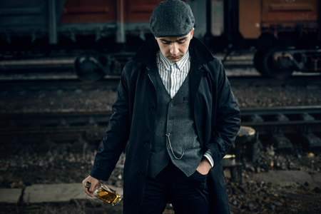 blinders: stylish gangster man with bottle whiskey in retro look posing on background of railway carriage. england in 1920s theme. fashionable brutal confident man