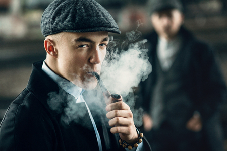 blinders: stylish men smoking in retro clothes posing on background of railway. england in 1920s theme. fashionable look of brutal confident man. atmospheric moments with smoke