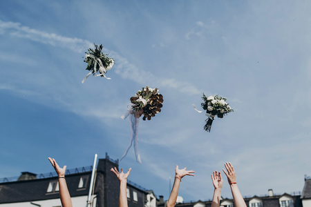 luxury bride and bridesmaids throwing up bouquets in sky, sunny wedding reception.  space for text. joyful moment. bride with girls having fun in wedding morning
