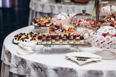 delicious candy bar at luxury  wedding reception. exclusive expensive catering. table with modern desserts, cupcakes, sweets with fruits. space for text. baby or bridal shower. holiday celebration 版權商用圖片 - 75805303