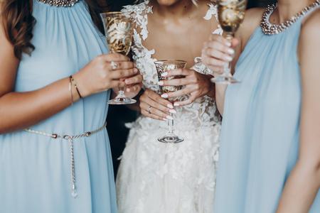 Concepto de vida de lujo. Hermosa novia y damas de honor brindando con champaña y divirtiéndose en la habitación del hotel, mañana de la boda. Manos sosteniendo elegantes gafas con bebidas. espacio para texto. Foto de archivo - 75805325