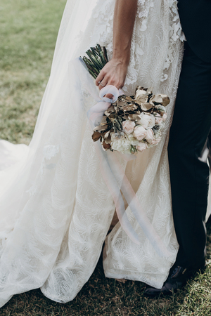stylish bride holding golden bouquet of roses with ribbons, standing and hugging with groom. space for text. sunny wedding day. luxury wedding reception. amazing gown