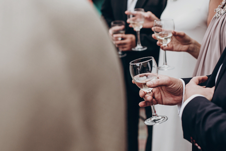 luxury life concept. champagne and wine glasses in hands at luxury wedding reception at restaurant. guests toasting and cheering at stylish celebration. space for text