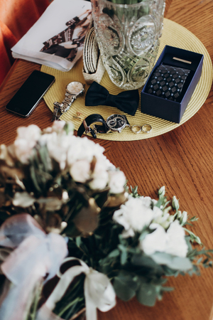 cuff link: stylish wedding rings bow tie watch and cuff links and bouquets for bride and groom. luxury roses and golden leaves, and man set on wooden table. morning preparation. space for text