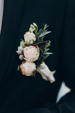 luxury boutonniere with roses on groom stylish suit. space for text. sunny wedding day. pink flowers and green leaves on tuxedo chest. modern look, close-up