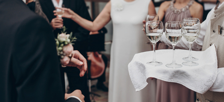 luxury life concept. glasses with champagne and wine on tray at luxury wedding reception at  restaurant.  waiter serving drinks among guests at stylish celebration. space for text