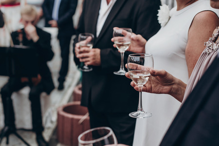 people toasting with champagne and wine glasses in hands at luxury wedding reception at restaurant. cheering at stylish celebration. luxury life concept. space for text