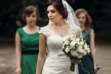 Beautiful brunette bride in vintage white wedding dress with fresh white roses bouquet walking with stylish bridesmaids in green dresses in summer park, newlywed woman with friends Stock Photo