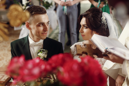 Emotional couple at wedding ceremony in christian catholic church, taking vows with priest and holy bible at the altar, faces closeup