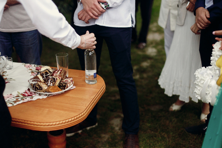 Traditional ukrainian wedding table for guests before ceremony, stylish man drinking and toasting vodka drinks near wooden table with tasty deserts, outdoors