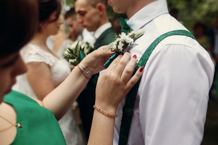 Beautiful bride in vintage wedding dress putting on boutonniere on handsome groom and his stylish groomsmen outdoors before the ceremony, hands and flowers closeup 스톡 콘텐츠