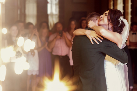 Romantic newlywed couple hugging, handsome groom and beautiful happy bride first dance while holding hands at restaurant wedding reception, beautiful lighting