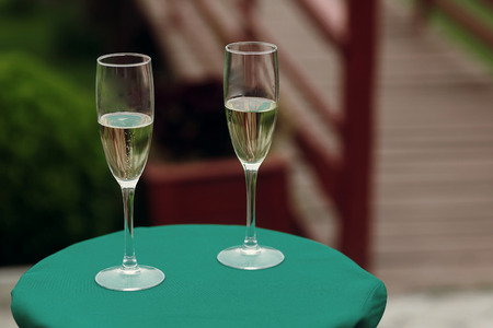 luxury glasses of champagne on green table at wedding outdoor reception and ceremony. catering in restaurant. celebration drinks. space for text Stock Photo