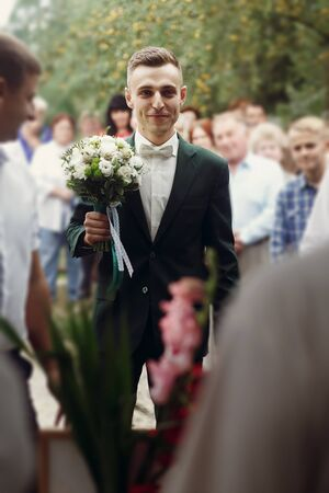 Handsome happy brunette groom in stylish black suit with white roses wedding bouquet walking to office for ceremony with guests and groomsmen