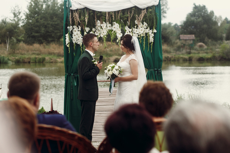 taking a wife: Handsome emotional groom in stylish suit giving wedding vow to beautiful bride with bouquet at outdoor wedding ceremony near aisle and lake, guests in the foreground Stock Photo