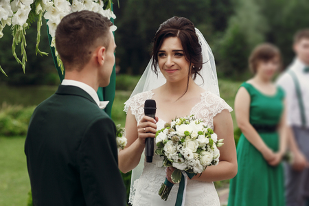 taking a wife: Gorgeous emotional bride in stylish white wedding dress with bouquet taking vow during outdoor wedding ceremony near aisle to handsome groom, her eyes tearing up