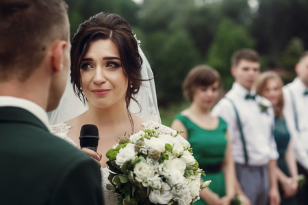 gorgeous bride crying while making vows on aisle at lake at wedding outdoor reception and ceremony. luxury wedding emotional couple