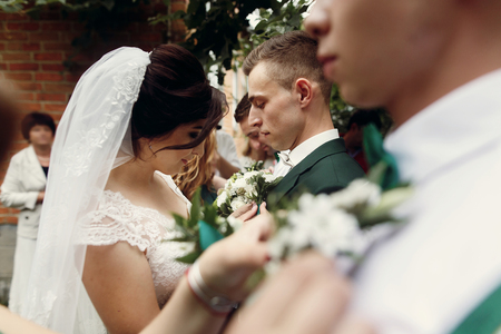 Beautiful bride in vintage wedding dress putting on boutonniere on handsome groom and his stylish groomsmen outdoors before the ceremony, hands and flowers closeup Stock Photo