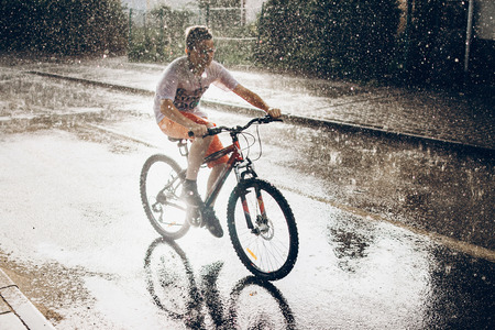 young boy riding bicycle in rainy street in sunshine, summer moments. space for text. atmospheric moment. cycling and activity. stylish hipster having fun under rain